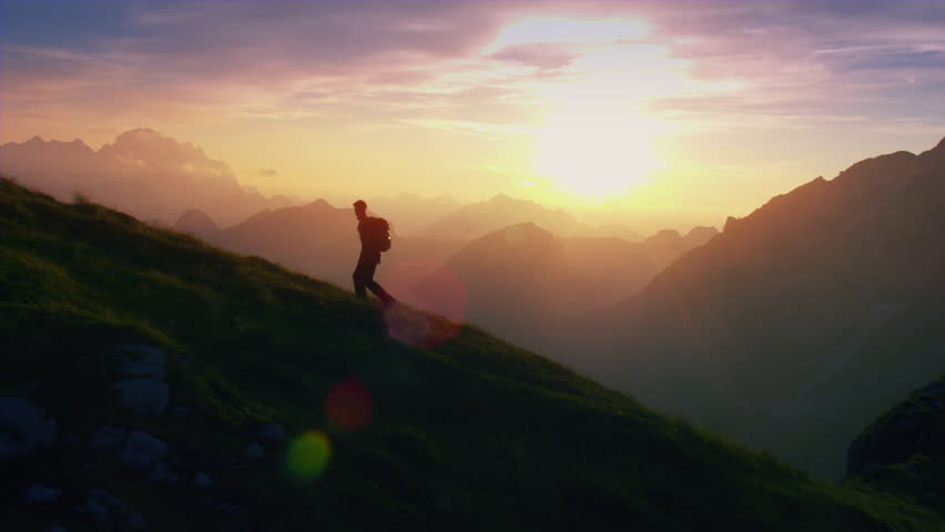 Aerial - Epic shot of a man hiking on the edge of the mountain as a silhouette in colorful sunset (edited version)