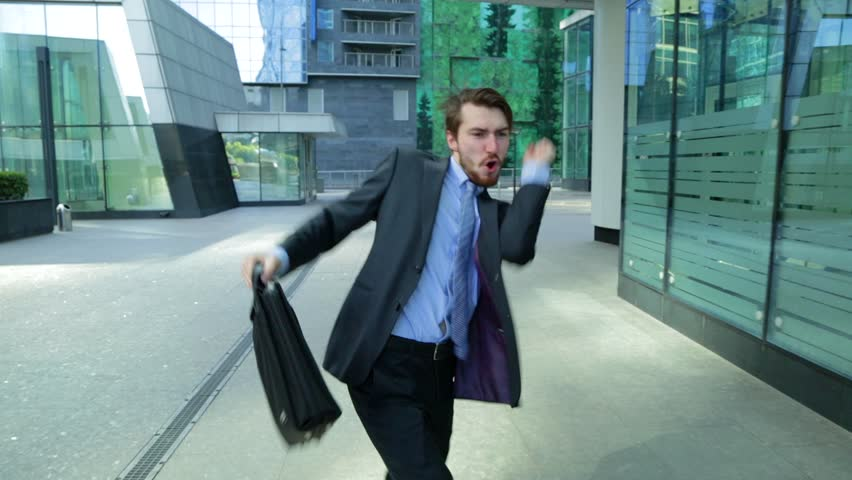 Happy businessman is dancing on the street near the office center wearing suit celebrating his achievements (steadicam shot) | Shutterstock HD Video #19254169