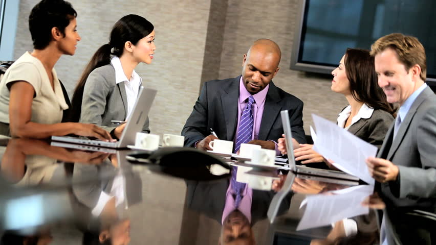 Team of five multi ethnic business people in city clothes meeting in a modern office boardroom | Shutterstock HD Video #1925443