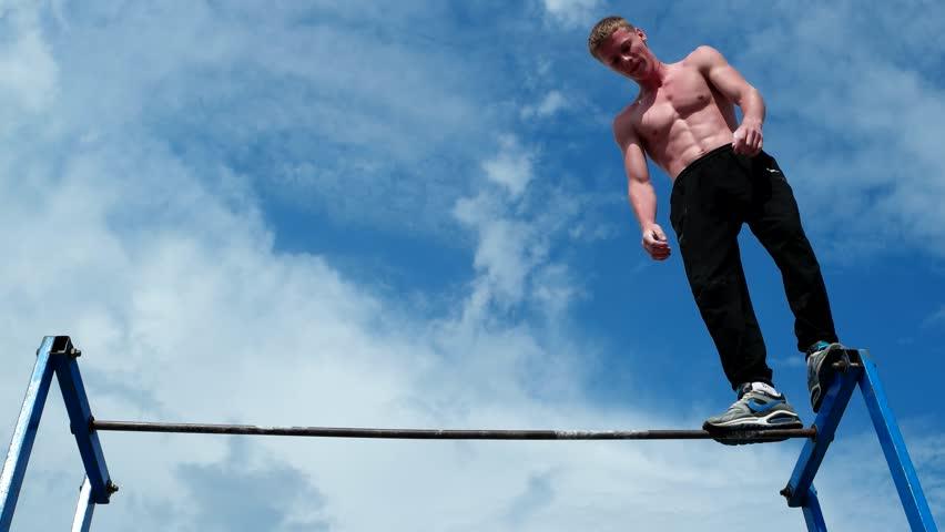 Kherson, Ukraine - 01 june 2016: The athlete performs exercises on the cross-bar, horizontal bar in Kherson 01 june 2016. Male athlete performs exercises on the horizontal bar, beautiful torso athlete #19265995