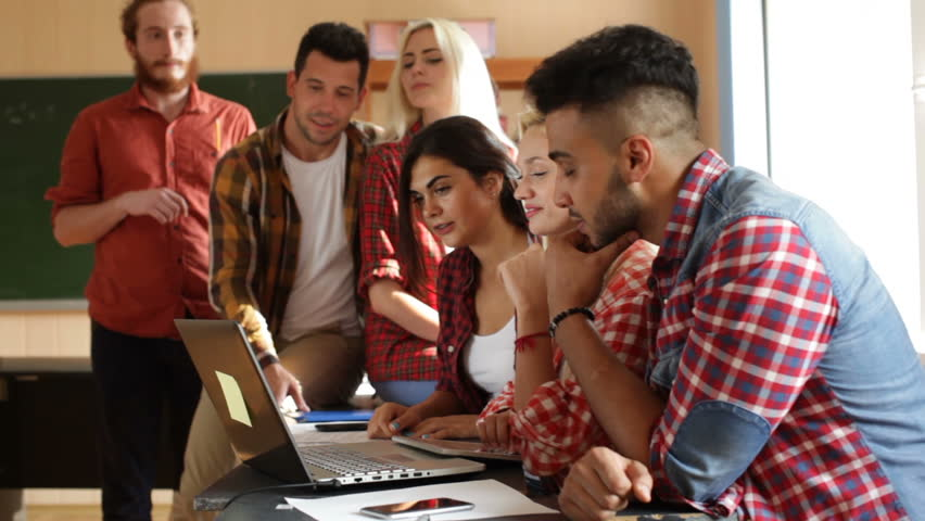 Students using laptop computer people group smile discussing sitting desk university classroom | Shutterstock HD Video #19276012