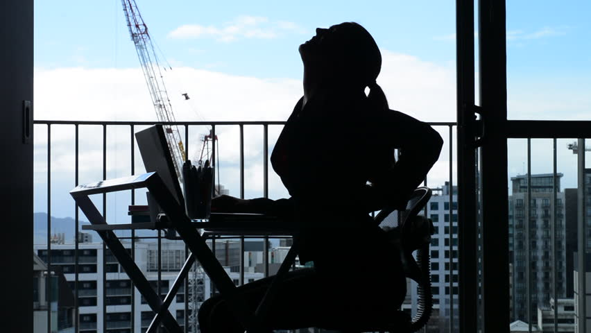 Silhouette of Young woman (age 30-40) having back pain while working at desk in office. Woman work healthcare lifestyle concept. Real people. copy space