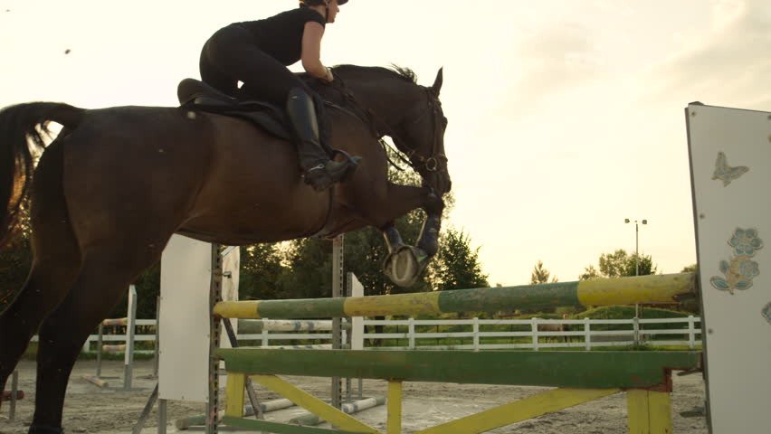 SLOW MOTION, CLOSE UP: Young horsegirl horseback riding strong brown horse jumping the fence in sunny outdoors sandy parkour riding arena. Competitive rider training jumping over obstacles at sunset