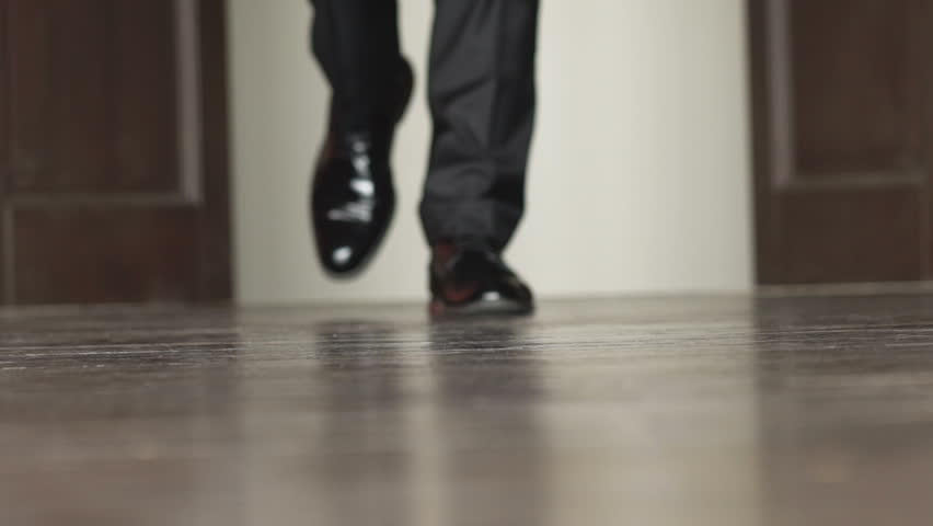 Unrecognizable businessman walking in the office. Slow motion