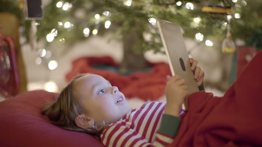 Closeup Of Little Boy Intently Watching A Video On His Tablet Underneath A Christmas Tree | Shutterstock HD Video #19334191
