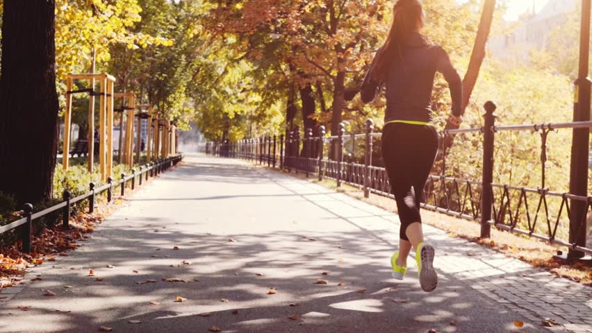 Runner Woman Running in the Sunny City Park Exercising Outdoors. Steadicam STABILIZED shot, SLOW MOTION 120 fps. Sportswoman Listening to Music during Morning Training. Healthy Lifestyle. Lens Flare. #19337212