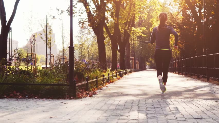 Runner Woman Running in the Sunny City Park Exercising Outdoors. Steadicam STABILIZED shot, SLOW MOTION 120 fps. Sportswoman Listening to Music during Morning Training. Healthy Lifestyle. Lens Flare. #19337542