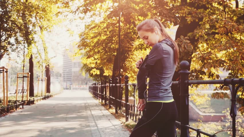 Runner woman running in park exercising outdoors. Steadicam STABILIZED shot, SLOW MOTION 120 fps. Athletic Sportswoman checking on Fitness app, Turning on Music, Using Smartphone. Lens Flare. #19344148