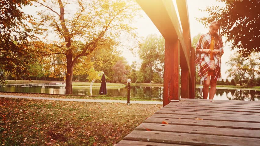 Woman Walking crossing Wooden Bridge in the Autumn Park. 4K. Unrecognizable young woman wearing denim sneakers shoes enjoying calm evening outdoors. Close up on boots.  #19344277