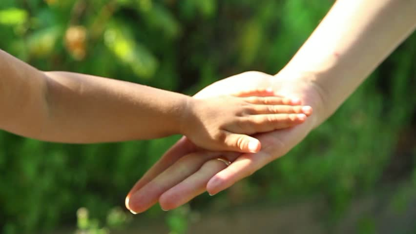 Close up of anonymous little child hands touching hands of her young mother with love. Happy family of mother and daughter having fun outside on summer day. Human hands at on green leaves background. | Shutterstock HD Video #19345702