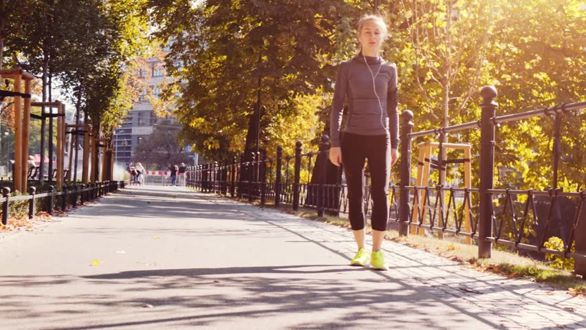 Runner Woman Running in the Sunny City Park Exercising Outdoors. 4K Steadicam STABILIZED shot. Sportswoman Listening to Music during Morning Training. Healthy Lifestyle. Lens Flare. #19353136