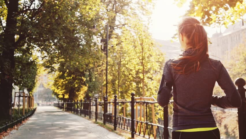 Runner Woman Running in the Sunny City Park Exercising Outdoors. Steadicam STABILIZED shot, SLOW MOTION 240 fps. Sportswoman Listening to Music during Morning Training. Healthy Lifestyle. Lens Flare. | Shutterstock HD Video #19353142