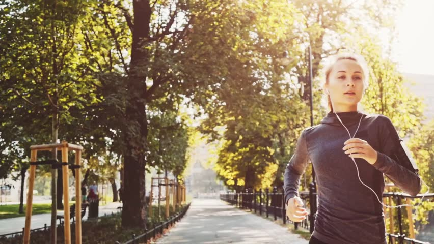 Runner Woman Running in the Sunny City Park Exercising Outdoors. Steadicam STABILIZED shot, SLOW MOTION 240 fps. Sportswoman Listening to Music during Morning Training. Healthy Lifestyle. Lens Flare. #19353346
