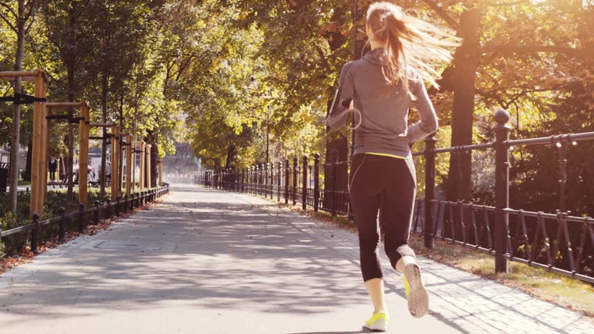 Runner Woman Running in the Sunny City Park Exercising Outdoors. 4K Steadicam STABILIZED shot. Sportswoman Listening to Music during Morning Training. Healthy Lifestyle. Lens Flare. #19353358