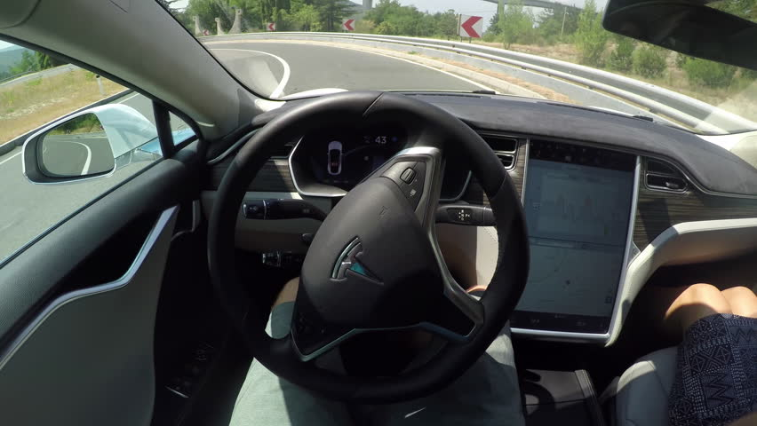 CRNI KAL, SLOVENIA - JULY 20: Eco friendly autonomous car using sensors, navigating with traffic-aware cruise control and driving with autosteer. Unrecognizable person using autopilot on sharp curve