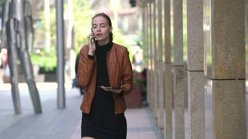 Beautiful young business woman with tablet talking on cellphone on street #19366222