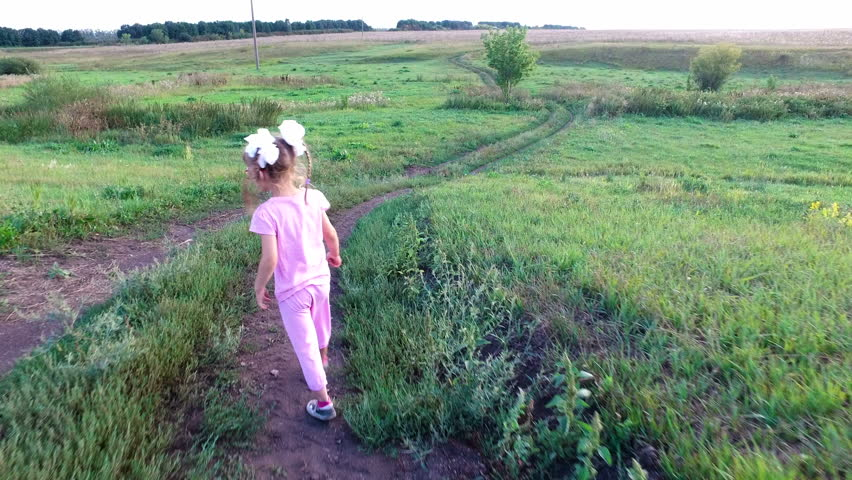 Girl child with glasses goes on the field road. The road descends into the ravine. Summer sunny evening at sunset.  | Shutterstock HD Video #19366333