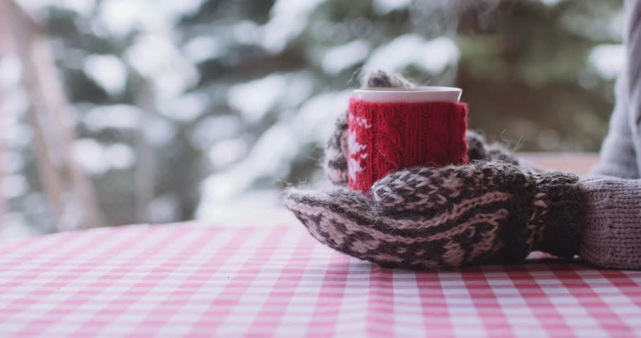 Woman Drinks Hot Tea or Coffee From Cup at Cozy Snowy House Garden on Winter Morning. 4K DCi SLOW MOTION 120 fps. Beautiful Girl Enjoying Winter Outdoors with a Mug of Warm Drink. Christmas Holidays