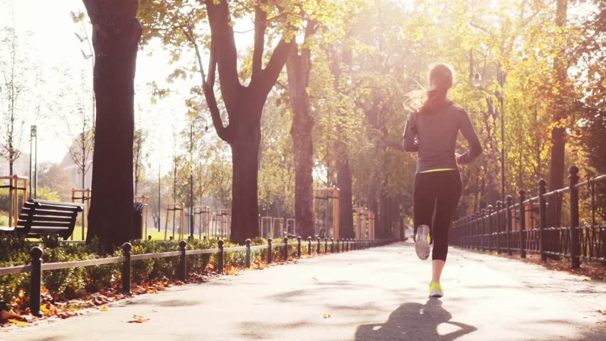 Runner Woman Running in the Sunny City Park Exercising Outdoors. Steadicam STABILIZED shot, SLOW MOTION 120 fps. Sportswoman Listening to Music during Morning Training. Healthy Lifestyle. Lens Flare. #19368205