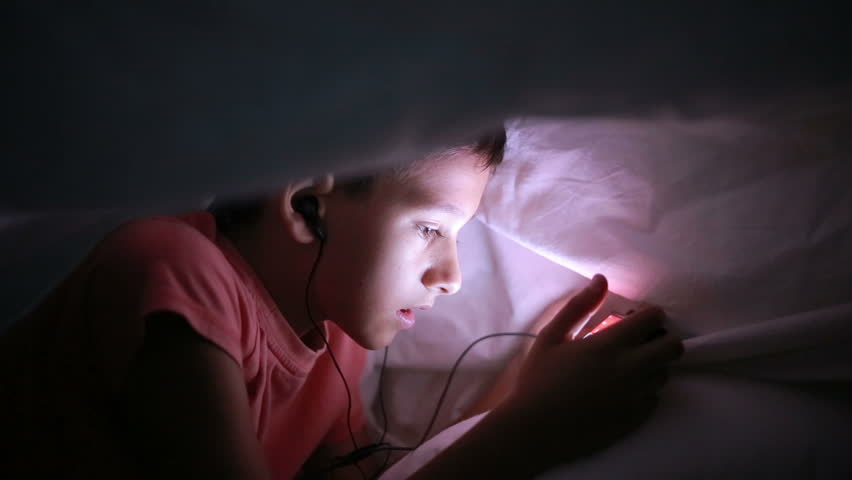 Young boy playing with a cellphone or smartphone on a bed. night | Shutterstock HD Video #19387732