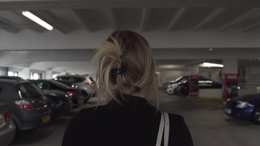 Attractive young blonde business woman walking in dark lonely car park parking garage