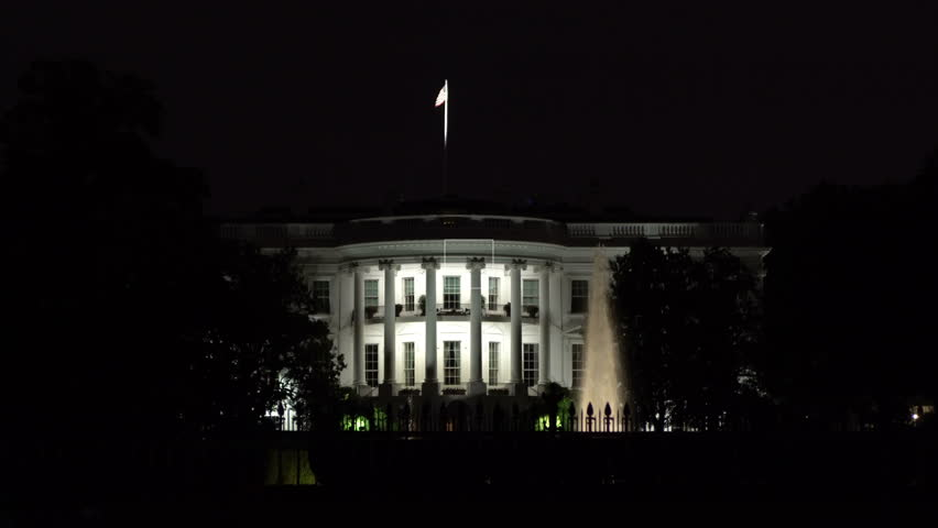 Washington DC - July 5th, 2016: The White House shot at night, US flag proudly flying on top.