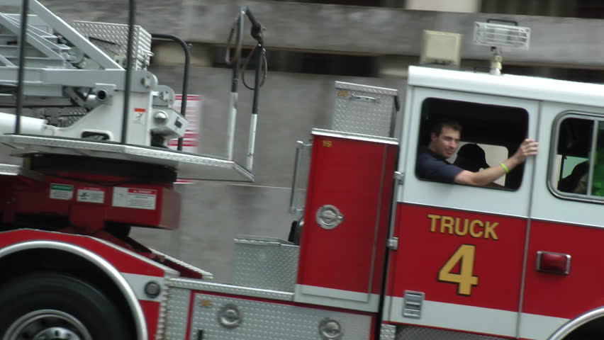 WASHINGTON, DC - CIRCA 2014:  Firefighter waves as aerial truck passes, responding, siren, weaves through traffic. In DC, EMS is part of Fire Department; & firefighters are often trained paramedics