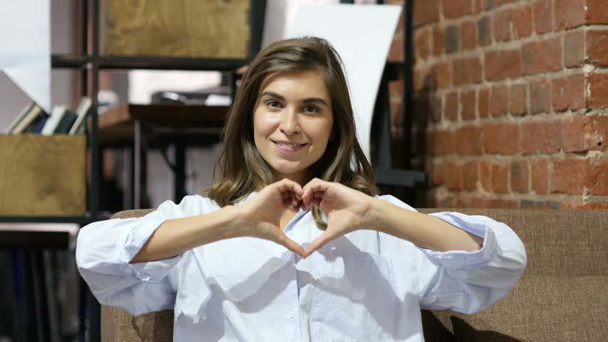 Heart Shape with HAnds by Young Lovely Girl Sitting on Sofa   Shutterstock HD Video #19436572
