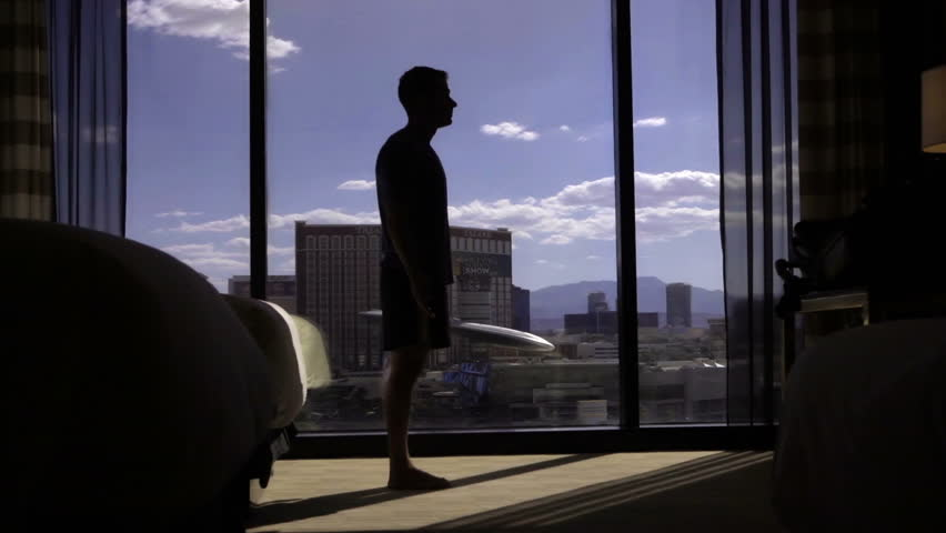 LAS VEGAS - AUGUST 6, 2016: man stretching to the sky in darkened hotel room in morning, yoga in LV. Las Vegas is the largest city in Nevada. | Shutterstock HD Video #19446649