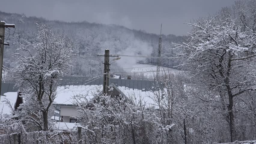 4K Aerial view of traditional house chimney smoke in cold winter day, snowy forest