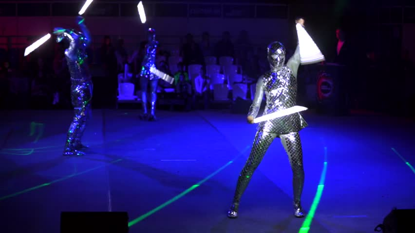 """MOSCOW, RUSSIA - JANUARY 30, 2016: Final of Moscow stage of National Cup of """"Robot wars-2016"""" at VDNH. A few people perform on arena in darkness in strange alien costumes and with lightsabers #19470265"""