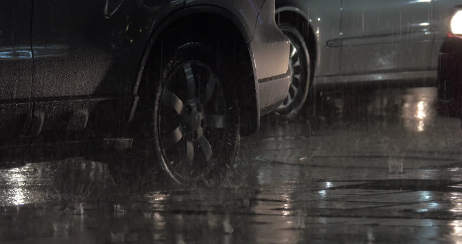 Two cars parked at the roadside under the heavy rain in night city. Logo washed out