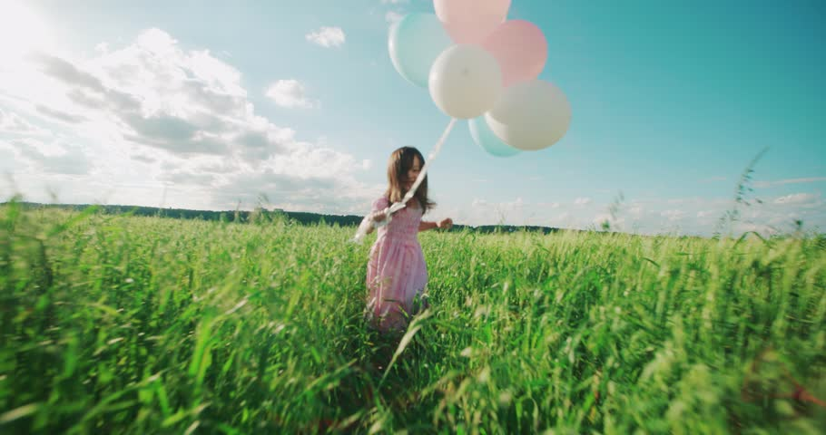 Little Asian girl in a dress running through green wheat field with balloons in hand, slow motion