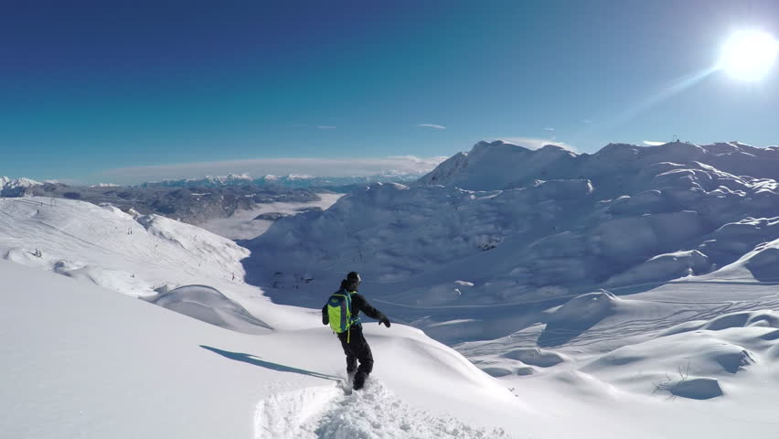 FOLLOW CLOSE UP: Happy snowboarder having fun snowboarding backcountry on a sunny winter day in snowy mountains. Extreme freeride snowboarder riding fresh powder snow off piste in mountain ski resort