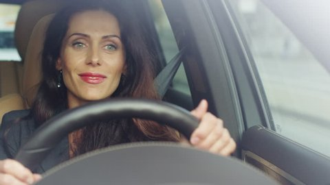 Excited Attractive Business Woman Listening to Music While Driving a Car.Shot on RED Cinema Camera in 4K (UHD).
