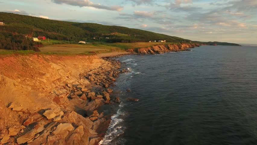 An aerial shot of a beautiful sunset on the coastline over the ocean in Cape Breton island Nova Scotia Canada