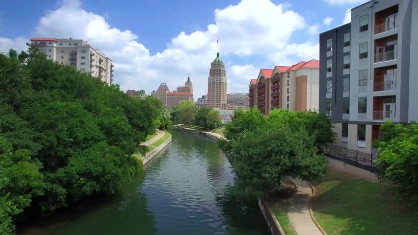 Aerial view of San Antonio riverwalk by skyline under sunny blue sky