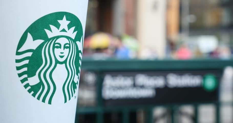 NEW YORK - CIRCA MAY, 2015: Starbucks Hot beverage coffee on table at Astor Place subway station with blurred people in background walking. Starbucks is the largest coffeehouse company in the world.