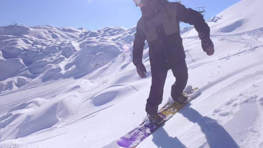 FIRST PERSON VIEW CLOSE UP: Extreme snowboarder riding fresh powder snow down the steep mountain slope, jumping over rocky overhangs. Freeride snowboarder having fun in backcountry mountain ski resort