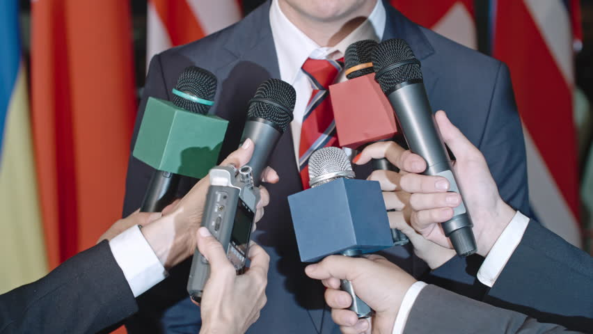 Mid-section of gesturing politician answering questions and talking into microphones and dictation machines of journalists at international convention