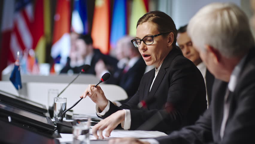 Profile of female politician in glasses reading aloud information from handouts and speaking into microphone at political convention   Shutterstock HD Video #19522663