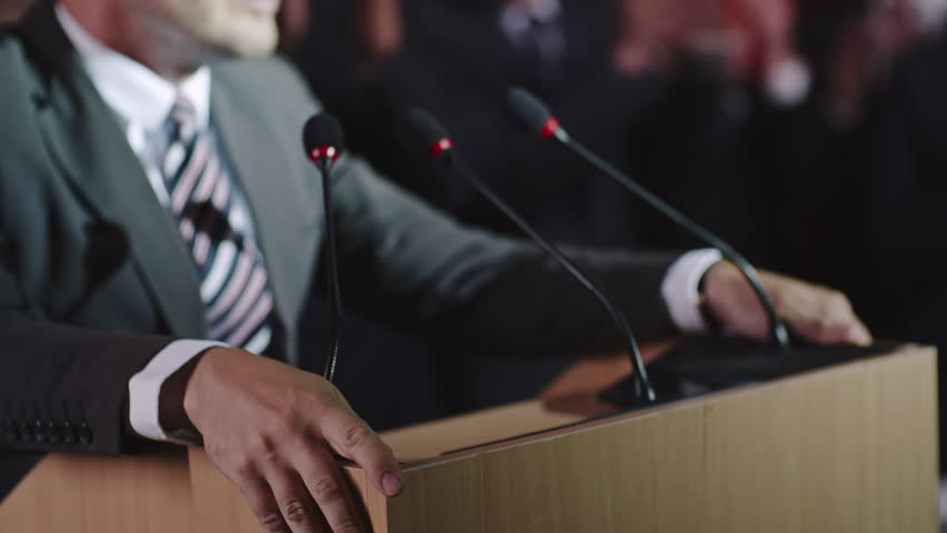 Closeup with selective focus of male politician hands lying on tribune as he delivering passionate speech before public, then making a fist and wildly gesturing   Shutterstock HD Video #19522696