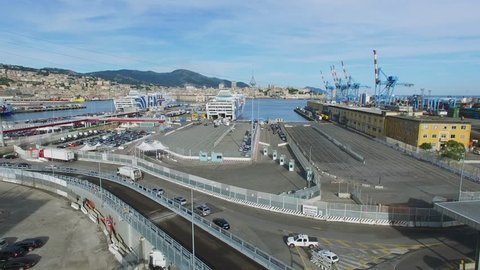 GENOA, ITALY - AUG 05, 2016: Many cars ride to ferryboats in Passengers Port and cityscape at summer day. Aerial view