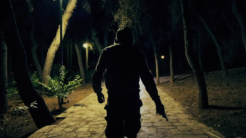 Hooded man walks in dark park draws knife,slomo 100p.A hooded onimous dark figure walks in a park at night and slowly draws out a blade.Slow motion 100fps.