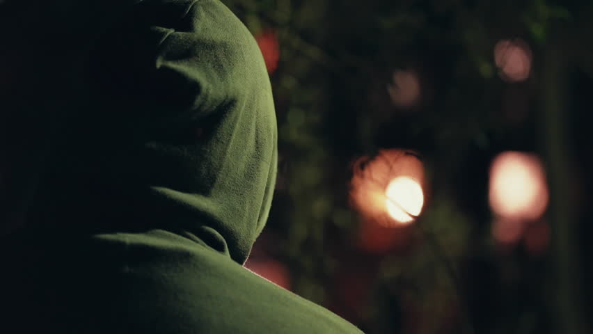 Hooded stalker stalking apartment from a distance at night,rack focus.A hooded ominous figure stalking a residential building at night | Shutterstock HD Video #19537486