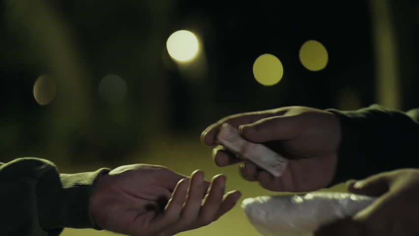 Two hands in dark park selling buying drugs hands cu transaction slow motion.Two men in a dark park at night exchange drugs hand to hand for money.Euro bills. | Shutterstock HD Video #19537558