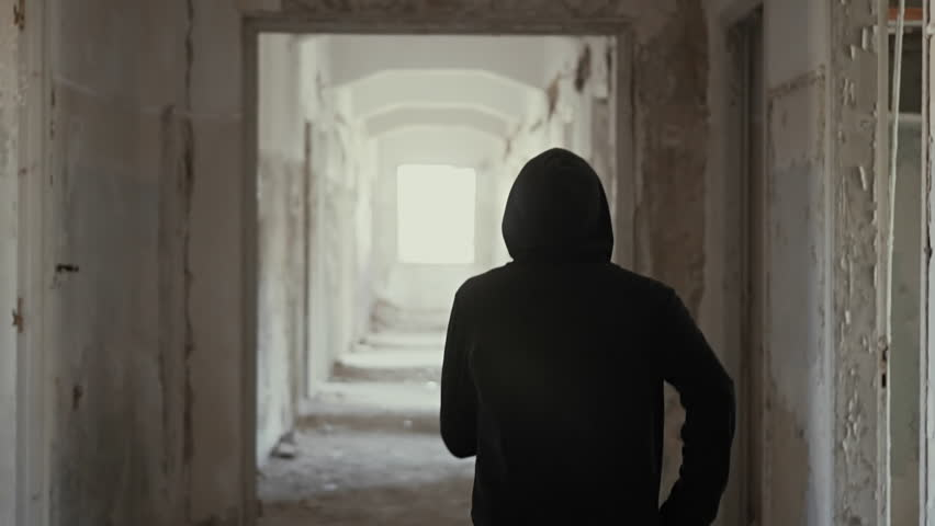 Hooded young man wondering inside destroyed abandoned building,slow motion,dramatic.Millenial with social issues, walks inside a big wrecked empty building in 100fps slow motion.Camera gimbal motion.