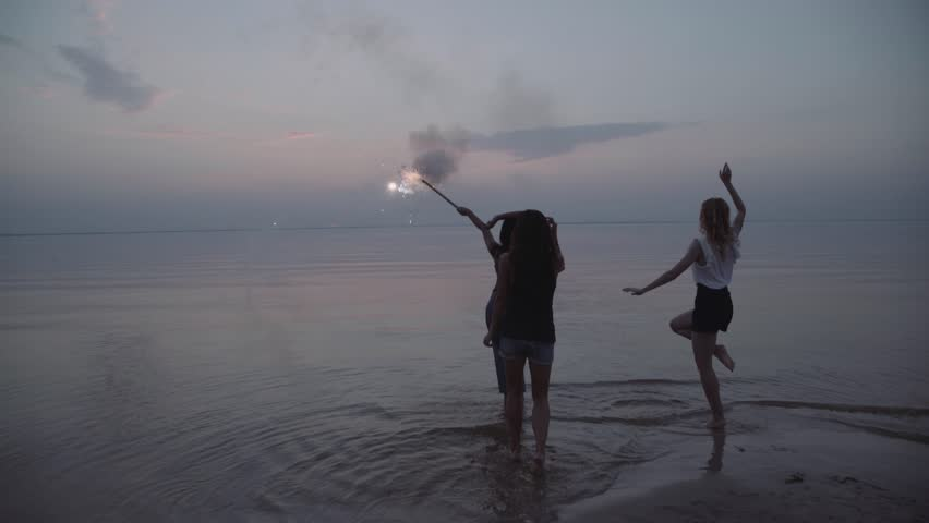 Rearview of mixed race friends dancing together on a beach shooting sparkling fireworks