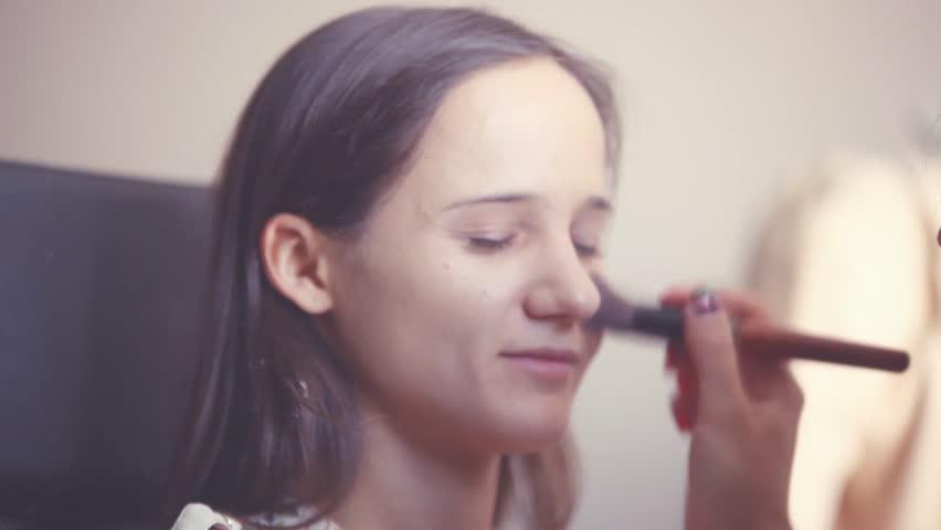Makeup artist makes a young woman beautiful makeup before an important event. Makeup Applying. 1920x1080   Shutterstock HD Video #19588429