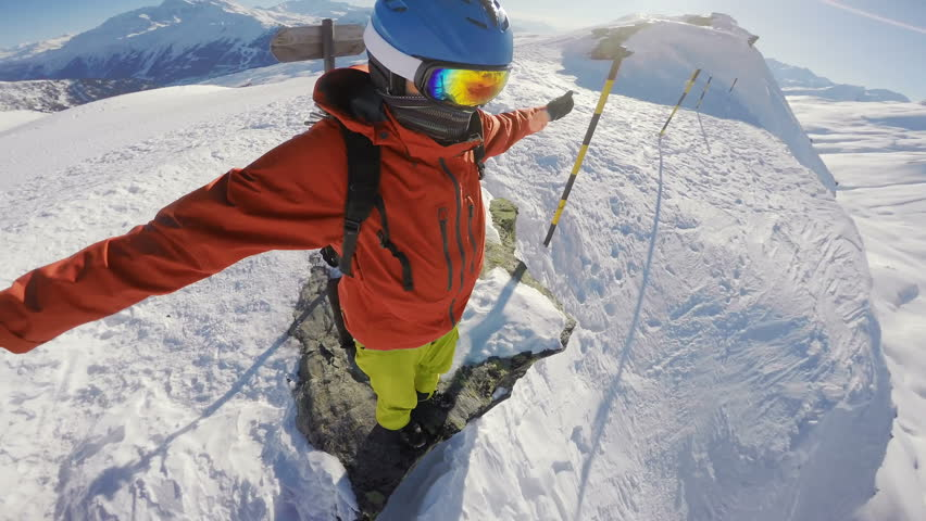 Snowboarder on top of the world, standing on the hill edge, looking down a mountain drop, arms outstretched, camera rotating around his head   Shutterstock HD Video #19591105
